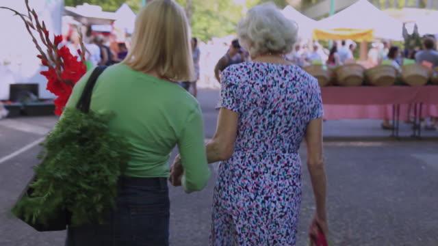 MS POV Senior woman with daughter walking at urban farmer's market / Portland, Oregon, USA