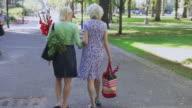 WS POV Senior woman with daughter walking away from urban farmer's market / Portland, Oregon, USA