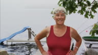 MS PORTRAIT Senior woman with hands on hip and wearing swim goggles looks at camera smiling / Waverly, Nova Scotia, Canada