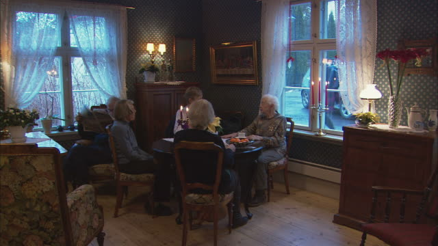 WS Senior women sitting behind table at nursery home, talking / Drobak, Akershus, Norway