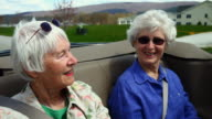 MS Senior women sitting in back of convertible car / Manchester, Vermont, USA