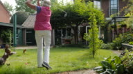 Seniors at Home: practicing golf swings in her garden