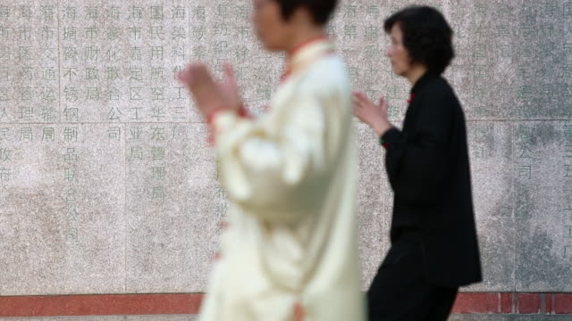 MS Seniors doing Tai Chi in the morning in front of chinese characters on wall.