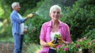 Seniors Gardening and Watering Plants