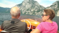 Seniors Taking on the World, active senior couple driving with electric boat on mountain lake