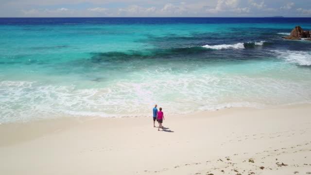 Seniors Taking on the World, drone video senior couple walking along beach