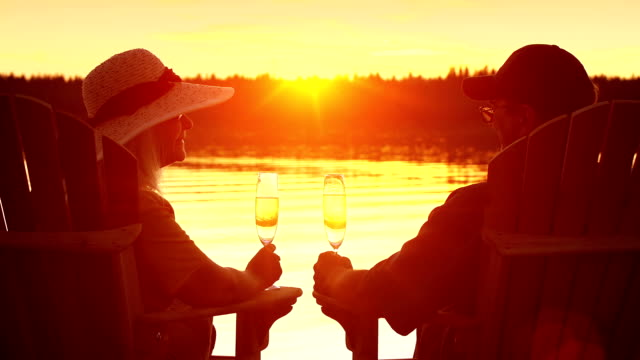 Seniors toast in their retirement by a lake.