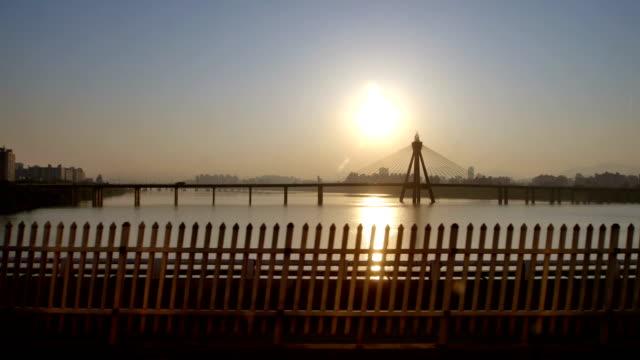 Seoul Subway train crossing Han river at sunset