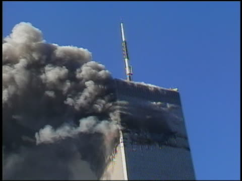 September 11 2001 medium shot helicopter / zoom out smoke from WTC Tower / tower collapsing / tilt down people running