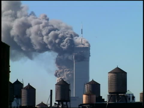 September 11 2001 wide shot WTC Towers burn / South Tower collapsing / water towers in foreground / NYC