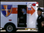 September 12 2001 MONTAGE Paramedic removing evidence bags from ambulance in front of St Vincent's Hospital while medical workers sit in waiting with...