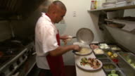 September 14 2009 MS Chef placing cooked meals on plates in restaurant kitchen / New Mexico United States