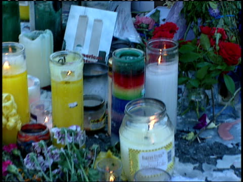 September 16 2001 PAN Flowers American flags candles and trinkets lying in memorial in Union Square Park while saxophonist plays photographer snaps...