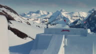 September 16 2009 MONTAGE A competing free skier freestyle jumping over a massive man made snow obstacle once at sunset / Oberstdorf Germany