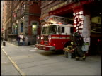 September 17 2001 TS Ladder truck driving out from Engine Company 39 building and two firemen climbing in with American flag flying at halfmast / New...