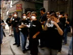 September 19 2001 MS Maskwearing workers gathered on a street corner outside a business playing patriotic Souza marches / New York City New York...