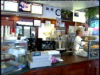 September 19 2001 MONTAGE Deli workers clean up behind counter and serve coffee to construction worker / New York City New York United States