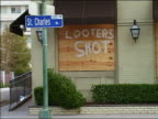 September 4 2005 Medium shot of 'Looters Shot' spraypainted on boarded up window with St Charles street sign in foreground after Hurricane Katrina /...