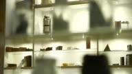 Sequence of focus pulls between various materials encased in specimen bottles lining glass shelves, UK.