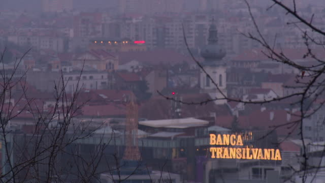 Sequence of focus pulls from bare branches onto illuminated signage reading 'Banca Transilvania', Cluj-Napoca, Romania.