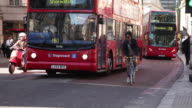 Sequence of tracking shots showing cyclists sharing the road with red double-decker buses and other vehicles near Liverpool Street Station, London, UK.