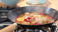 Sequence over a pan of sweet and sour chicken.