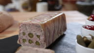 Sequence over a terrine on a kitchen worktop.