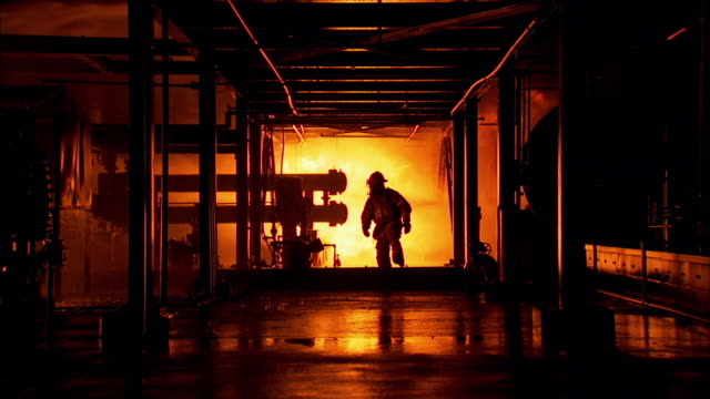 Sequence showing a fireman walking through a burning industrial building.