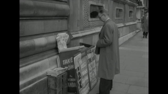 Sequence showing a man purchasing a newspaper from a self service stall
