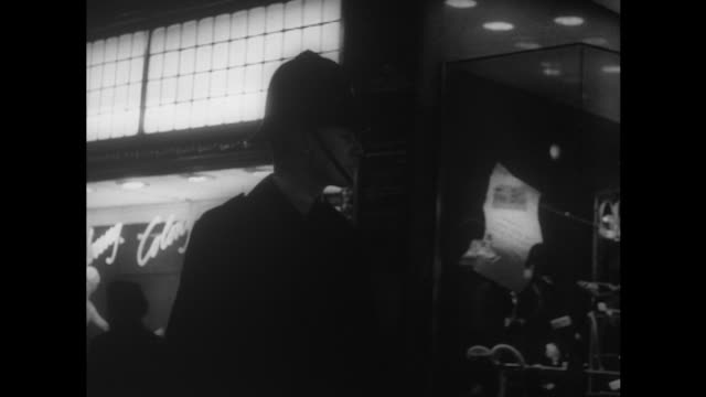 Sequence showing a policeman patrolling around shops at night