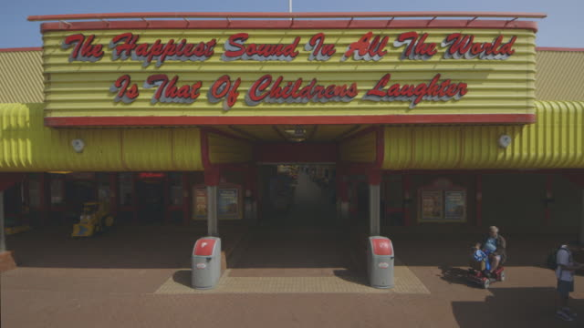 Sequence showing a retro sign above the amusements arcade of Walton-on-the-Naze's seaside pier, Essex, UK.