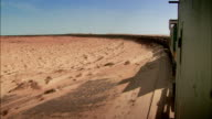 Sequence showing a vast freight train carrying iron ore across Mauritania.