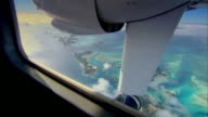 Sequence showing a view over the the Caribbean Sea and islands from a small aeroplane travelling from Nassau in the Bahamas to Long Island, Antigua and Barbuda.