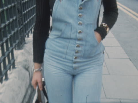 Sequence showing a woman walking along a street wearing denim dungarees