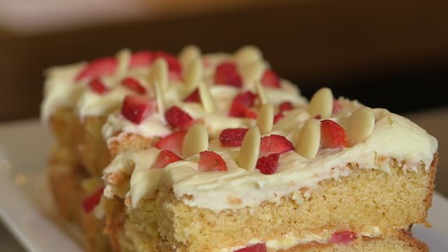 Sequence showing close-up views of cake on display in a cafe, UK.
