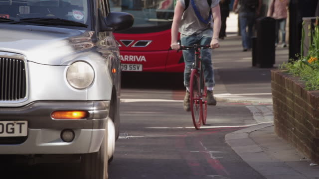 Sequence showing cyclists negotiating heavy buses and taxis on a busy London street near Liverpool Street Station, UK.