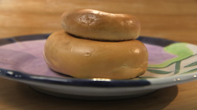 Sequence showing differently-sized bagels sitting on a purple plate in two different formations.