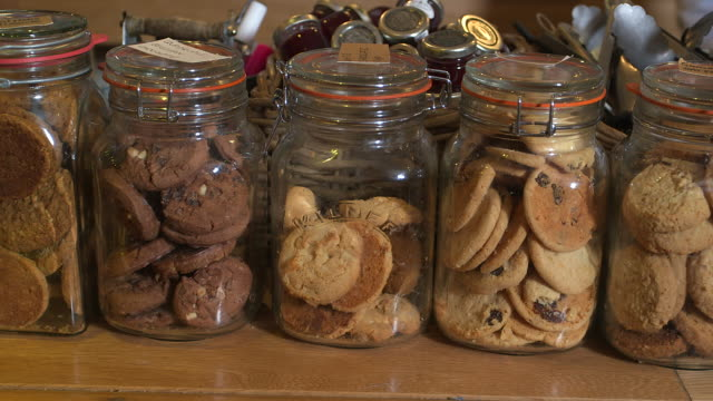 Sequence showing glass jars full of cookies and biscuits at a cafe in a UK.