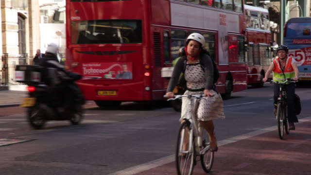 Sequence showing people cycling in a bus lane on a busy road outside Liverpool Street Station, London, UK.