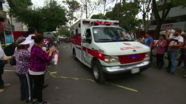 Sequence showing people in Mexico City after the earthquake of 19th September 2017 including people applauding an ambulance and views of military...