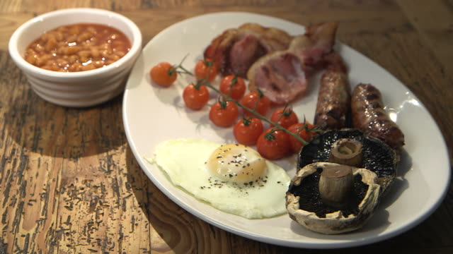Sequence showing steaming mushrooms on a traditional English fry-up, UK.