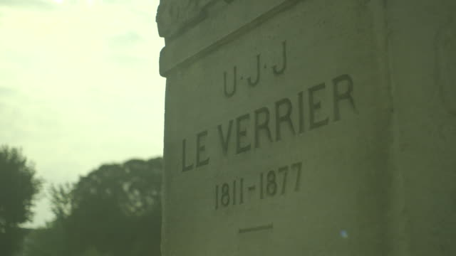 Sequence showing the base of a statue of Urbain Le Verrier, the French mathematician who discovered the planet Neptune, at the Observatoire de Paris in Paris' fifth arrondissement, France (with some sun flare).