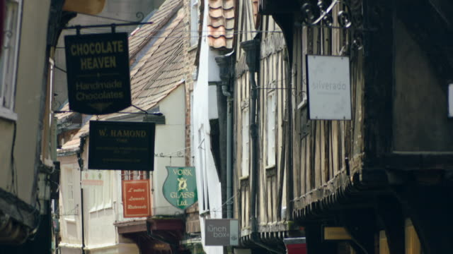 Sequence showing the boutique shops in timber-framed buildings of the narrow streets in York's city centre, Yorkshire, UK.