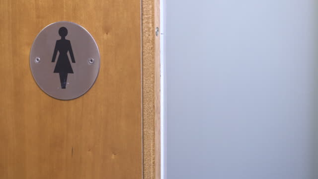 Sequence showing toilet doors with male and female symbols shutting, UK.