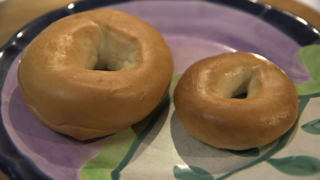 Sequence showing two bagels of different sizes on a painted plate.