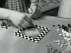 Sequence showing two women assembling a mosaic picture at a handicrafts exhibition at Earls Court exhibition hall