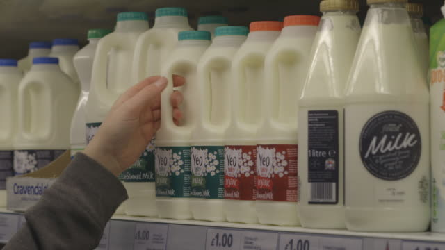 Sequence showing various brands of milk on refrigerated shelves at a large UK supermarket.