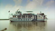 Sequence showing wide shots of a steamer-style cruising pleasure boat on the River Padma (known in India as the Ganges), Bangladesh.