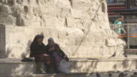 Sequence showing women chatting at the base of the Column of Constantine, also known as the Burnt Pillar or Stone, Istanbul, Turkey.
