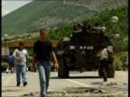 Serbian civilians and forces leave Prizren KOSOVO Prizren EXT NATO armoured vehicles manned by German troops along road and through check point near...